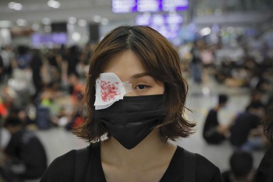홍콩 시위 참가자가 12일 홍콩국제공항에서 안대를 두른 채 집회에 참여했다. [AP=연합뉴스]