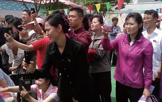 북한의 한 소학교(초등학교) 운동회에서 학부모들이 스마트폰으로 자녀들의 모습을 촬영하고 있다. [사진출처·북한 대외선전매체 웹사이트]