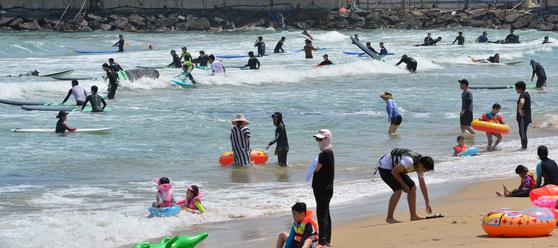 말복인 11일 한 해수욕장에서 피서객과 서퍼들이 더위를 식히고 있다. [뉴스1]
