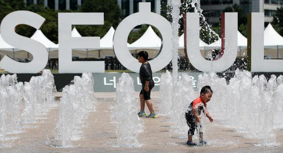 무더운 날씨를 보인 지난 10일 서울 중구 서울광장 분수대를 찾은 어린이들이 물놀이를 하며 더위를 식히고 있다. 태풍 레끼마가 지나간 뒤 13일 다시 서울에는 폭염경보가 발효됐다. [뉴스1]