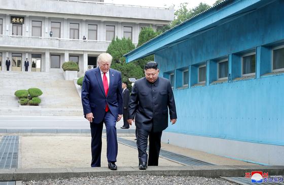 도널드 트럼프(왼쪽) 미국 대통령과 김정은 북한 국무위원장이 지난 6월 30일 오후 판문점에서 군사분계선을 넘고 있다. [연합뉴스]