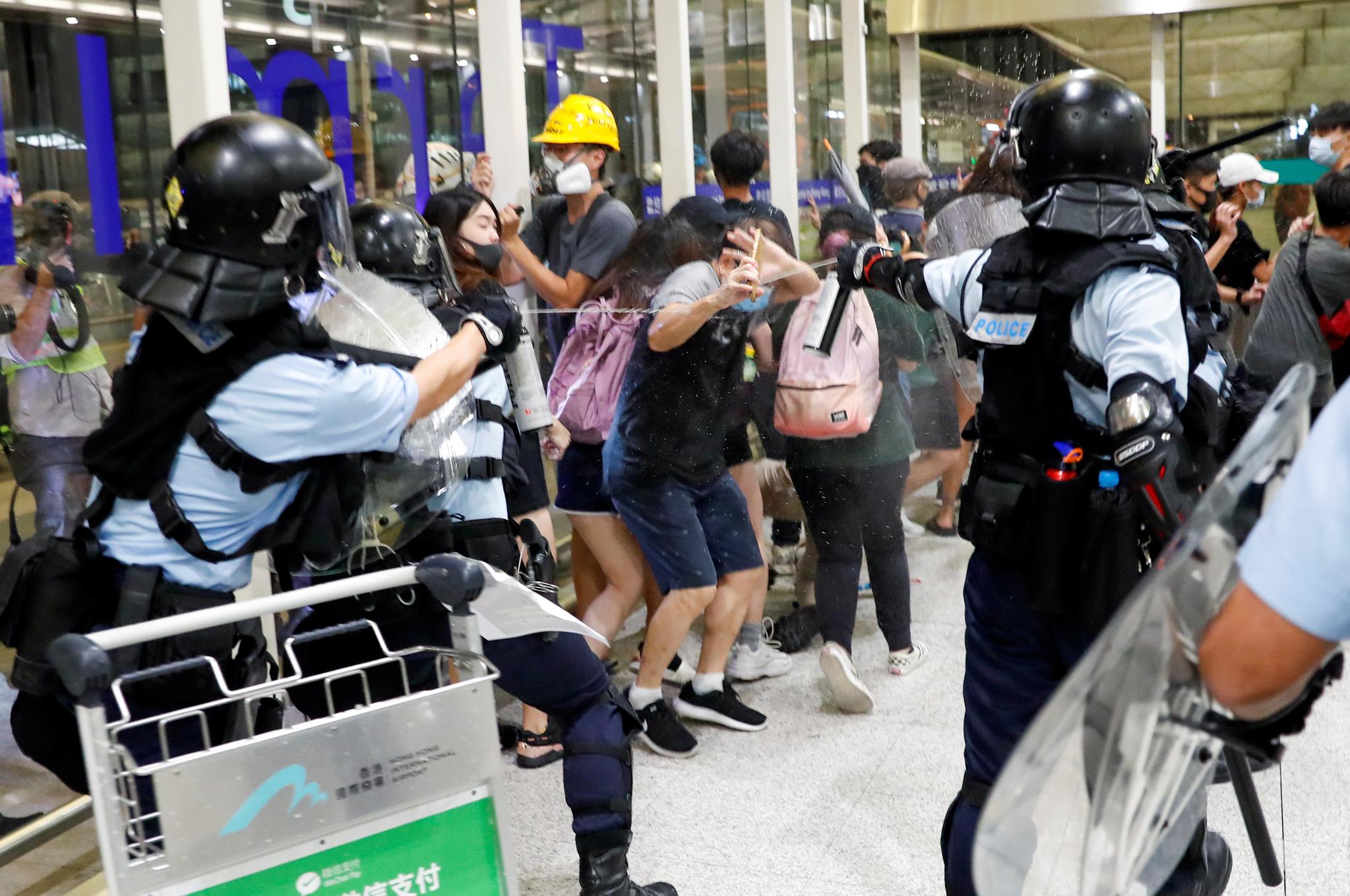 13일 반정부 시위대가 점거해 업무가 마비된 홍콩 국제공항에서 경찰이 시위대와 충돌하고 있다. 지난 11일 여성 시위 참가자가 경찰의 고무탄에 맞아 실명한 데 대해 시위대는 이틀째 공항을 밤샘점거했다.[로이터=연합뉴스]