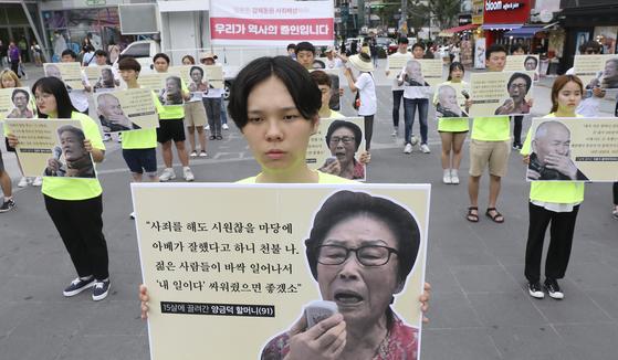 14일 오후 서울 서대문구 신촌 연세로 차없는 거리에서 국제평화행진 대학생 홍보단이 '우리가 역사의 증인입니다' 플래쉬몹을 하며 강제징용 피해자의 이야기가 담긴 피켓을 들고 있다. [뉴시스]