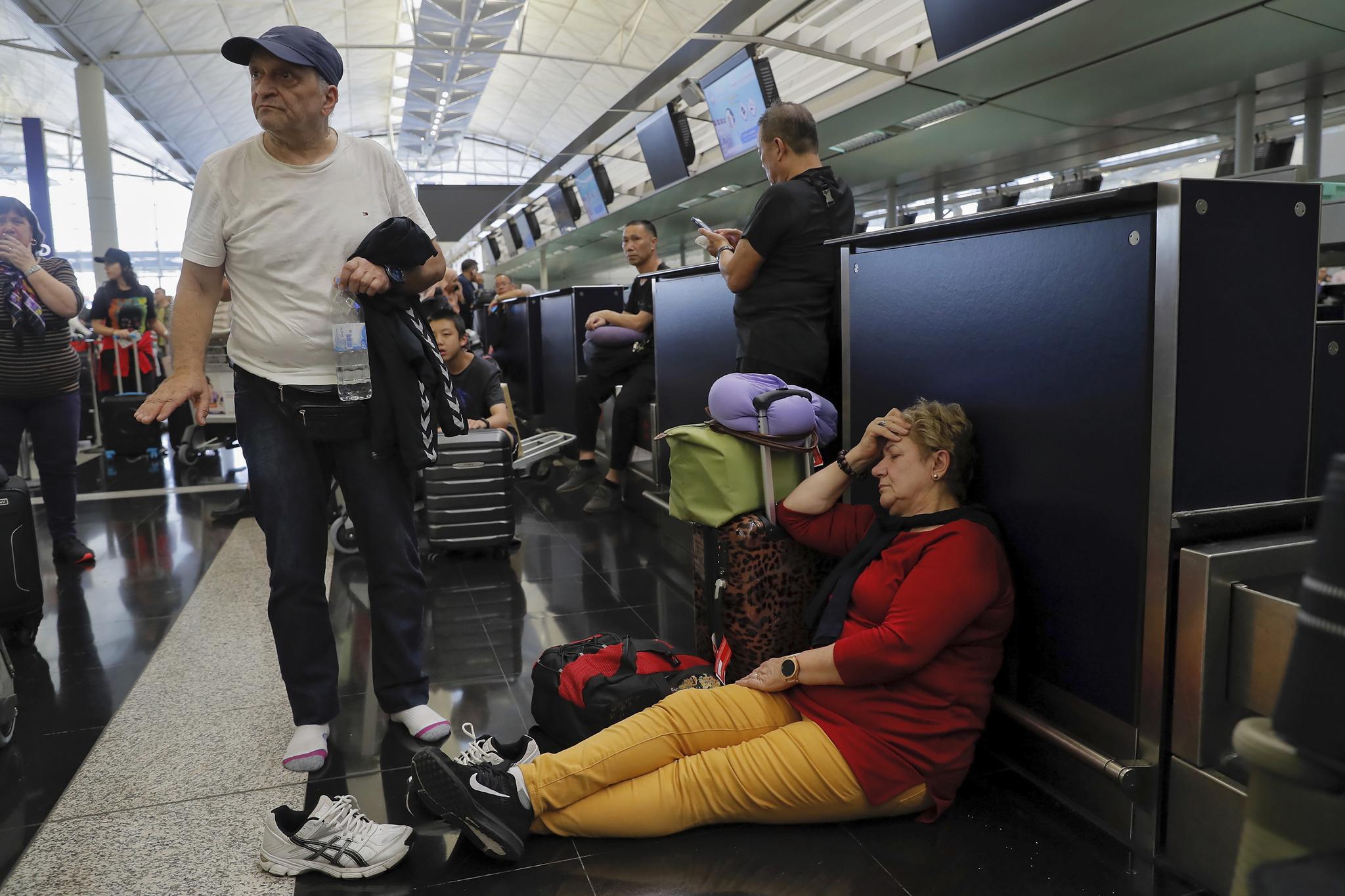 여행객들이 항공기 수속 창구가 운영을 중단하자 심각한 표정을 하고 있다. [AP=연합뉴스]