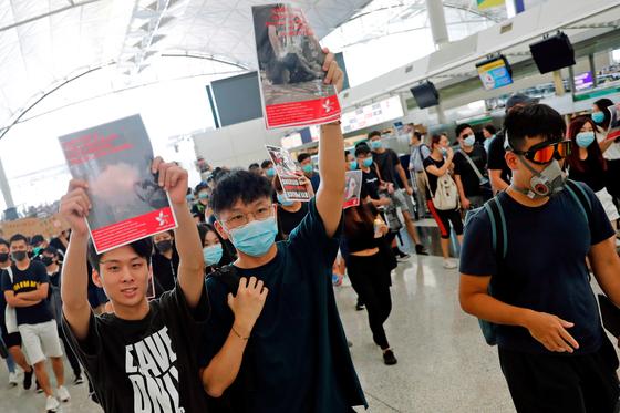 홍콩 시위대가 12일 홍콩 공항을 점거한 채 전날 시위에서 눈을 다친 여성의 사진을 보이며 항의하고 있다. [로이터=연합뉴스]