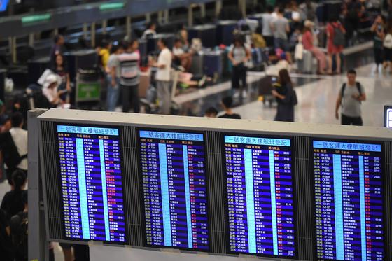 이틀째 밤샘 점거시위 후 14일 정상 운영에 들어간 홍콩 국제공항의 모니터에 항공기 운항 스케줄이 표시돼 있다. [홍콩 신화=연합뉴스]