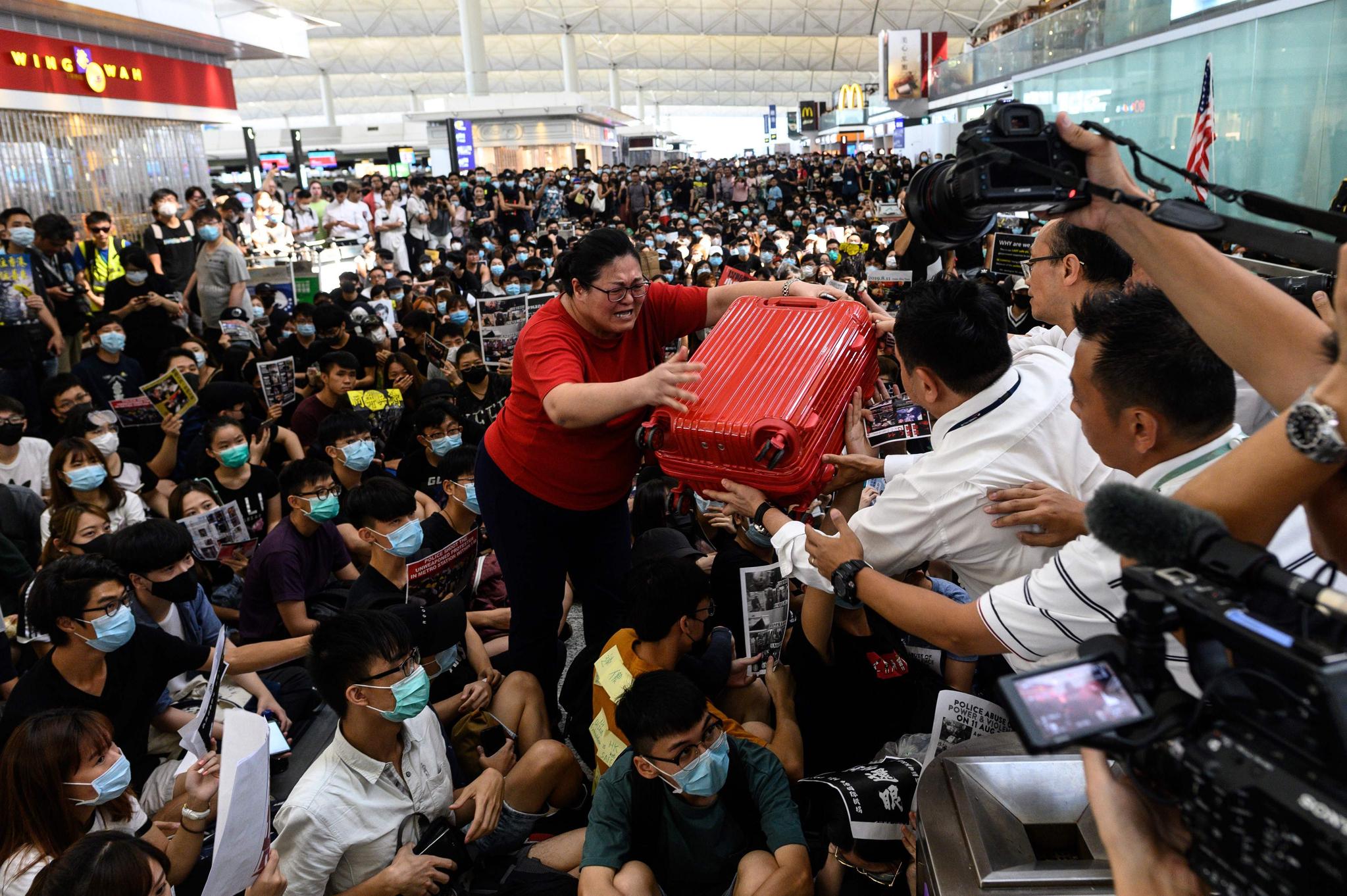한 여행객이 13일 홍콩국제공항에서 시위대 사이를 힘들게 지나 출국 게이트 앞에서 공항 직원들의 도움을 받고 있다. [AFP=연합뉴스]