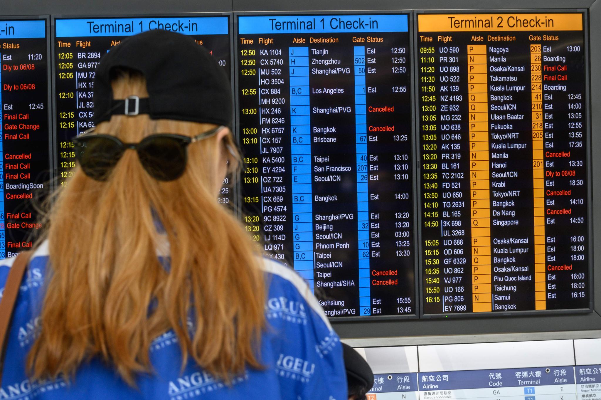 5일 홍콩에서 '범죄인 인도 법안'(송환법) 반대 총파업이 벌어진 가운데 홍콩 국제공항에서 한 승객이 탑승할 항공기 운항 상황을 확인하고 있다. [연합뉴스]