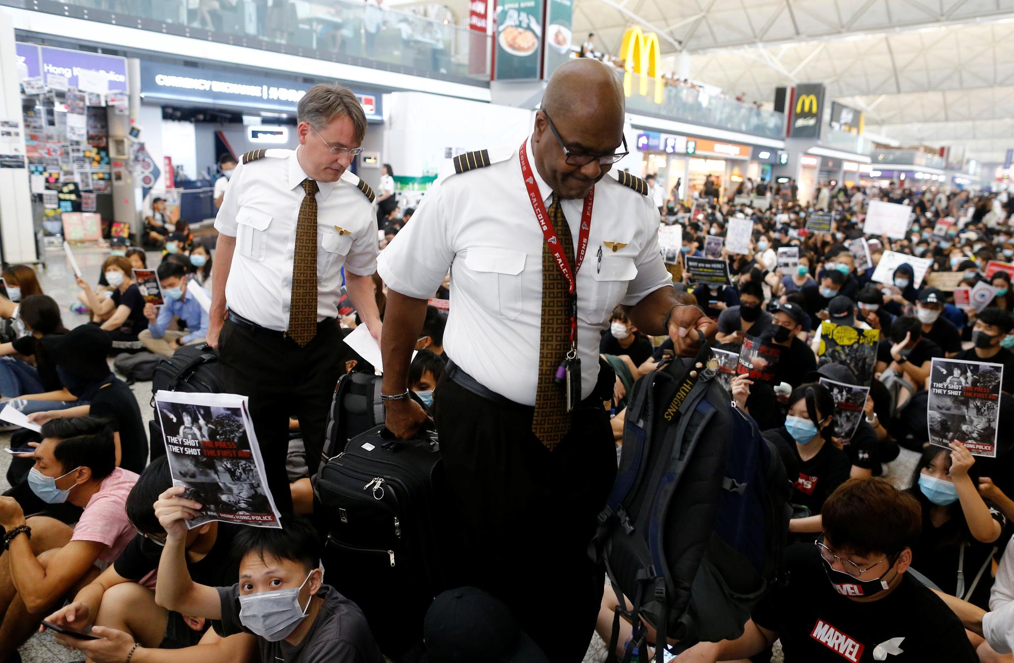 항공기 승무원들이 13일 홍콩국제공항에서 시위대를 지나 출국 게이트로 가고 있다. [로이터=연합뉴스]