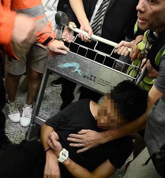 13일 밤 홍콩 공항에서 시위대에 붙들린 중국 남성이 중국에서 온 공안이라는 의혹 속에 구타를 당해 거의 실신 상태에 빠져 있다. [중국 환구망]