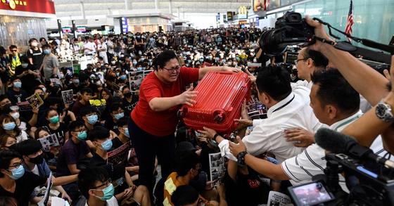 반정부 시위자들로 메워진 홍콩 국제공항에서 13일 출국장 안으로 들어가려는 한 관광객이 공항 직원에게 여행용 가방을 부탁하며 도움을 받고 있다. [AFP=연합뉴스]