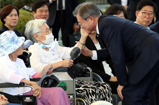 지난해 8월 14일 오후 충남 천안 국립 망향의 동산 안 모란묘역에서 열린 '일본군 위안부 피해자 기림의 날' 첫 정부 기념식에서 김경애 할머니가 문재인 대통령의 볼을 만지고 있다. 청와대 사진기자단