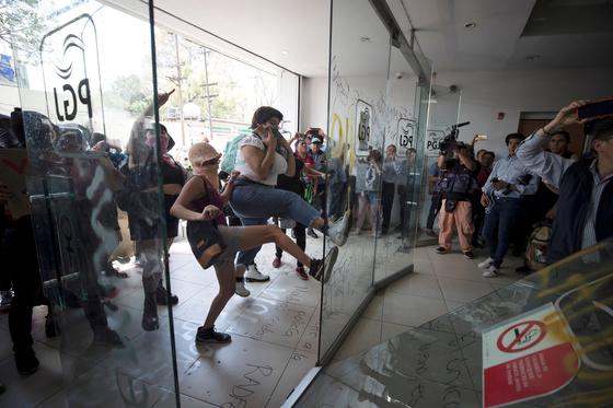 멕시코 여성 시위대가 12일(현지시간) 멕시코시티 공안부 청사 건물 출입문을 발로 차 넘어뜨리고 있다. [로이터=연합뉴스]