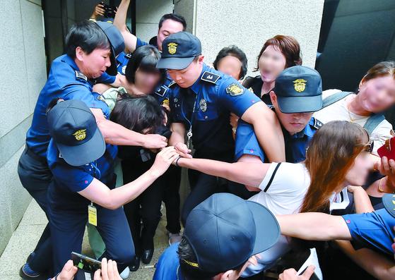 고유정의 첫 공판이 열린 12일 시민들이 호송차에 오르는 고유정의 머리채를 잡아 당기고 있다. [뉴시스]