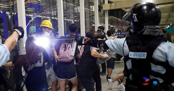 13일 밤 홍콩국제공항에서 진압 경찰이 반송환법 시위대를 향해 최루가스 스프레이를 뿌리고 있다. [로이터=연합뉴스]