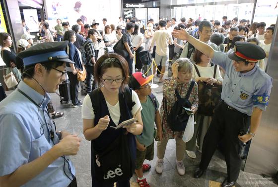 """일본 동남쪽에 위치한 하카타역에서 15일 기차 운행 여부를 묻는 시민들. 일본 서부지역 신칸센을 운영하는 JRwest는 """"태풍 크로사로 인해 15일 신칸센 운행이 중단될 것""""이라고 발표했다. [EPA=연합뉴스]"""