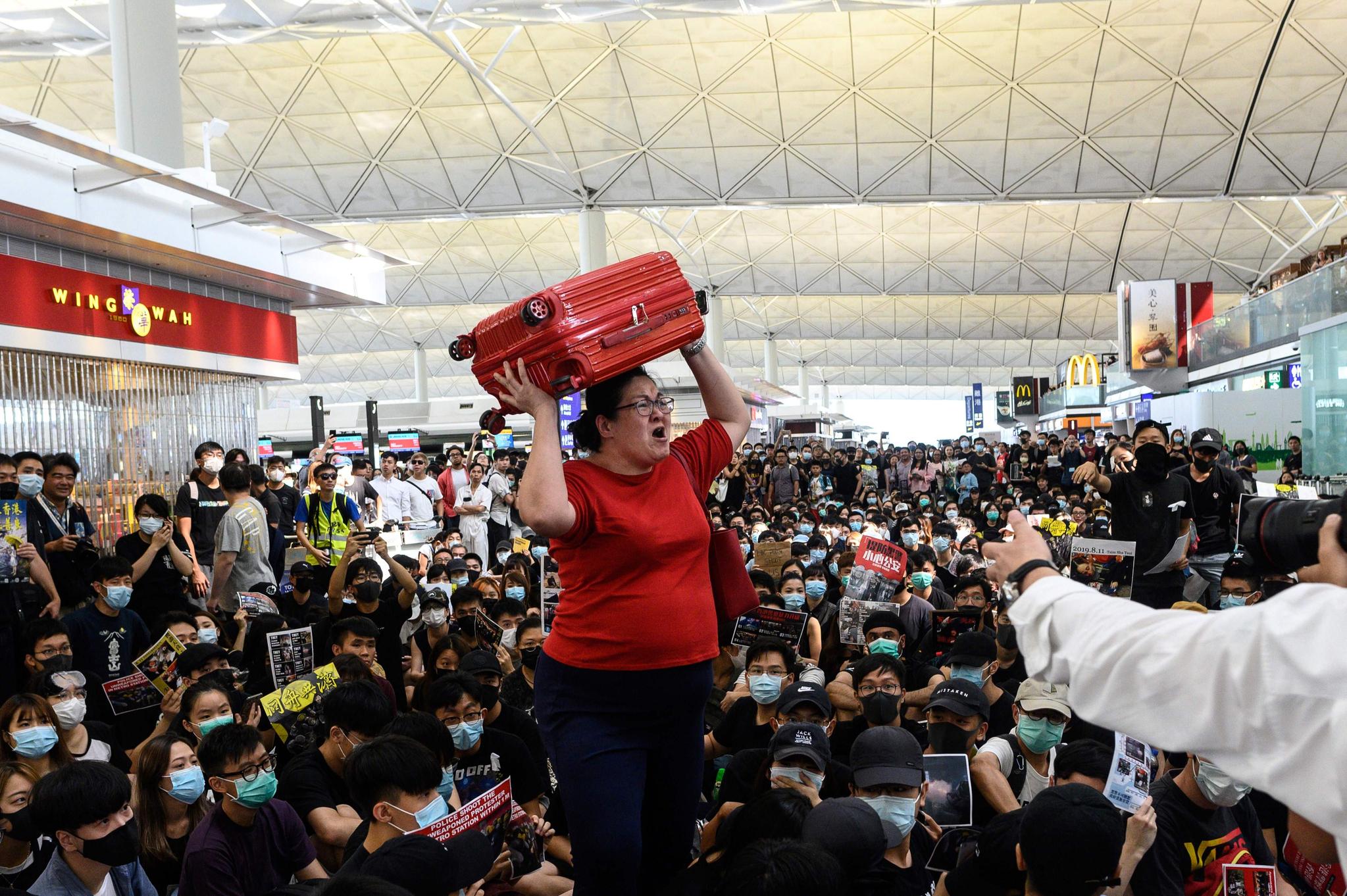 한 여행객이 13일(현지시간) 홍콩국제공항에서 가방을 머리에 이고 출국 게이트로 이동하며 공항 로비를 가득 메운 시위대에 항의하며 소리를 지르고 있다. [AFP=연합뉴스]