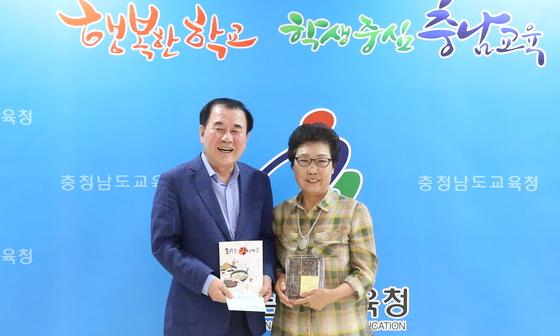 '요리는 감이여'라는 책을 만드는 데 참여한 김용선 할머니가 김지철 충남교육감(왼쪽)에게 책을 전달하고 있다. [사진 충남교육청]