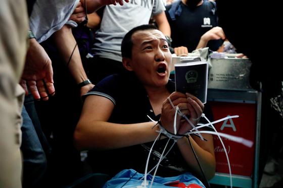 중국 관영매체 환구시보 기자로 밝혀진 푸 구오하오 (Fu Guohao)가 지난 13 일 밤 홍콩 국제공항에서 송환법 반대 시위대에 손이 묶인 채 억류되어 있다. [로이터=연합뉴스]