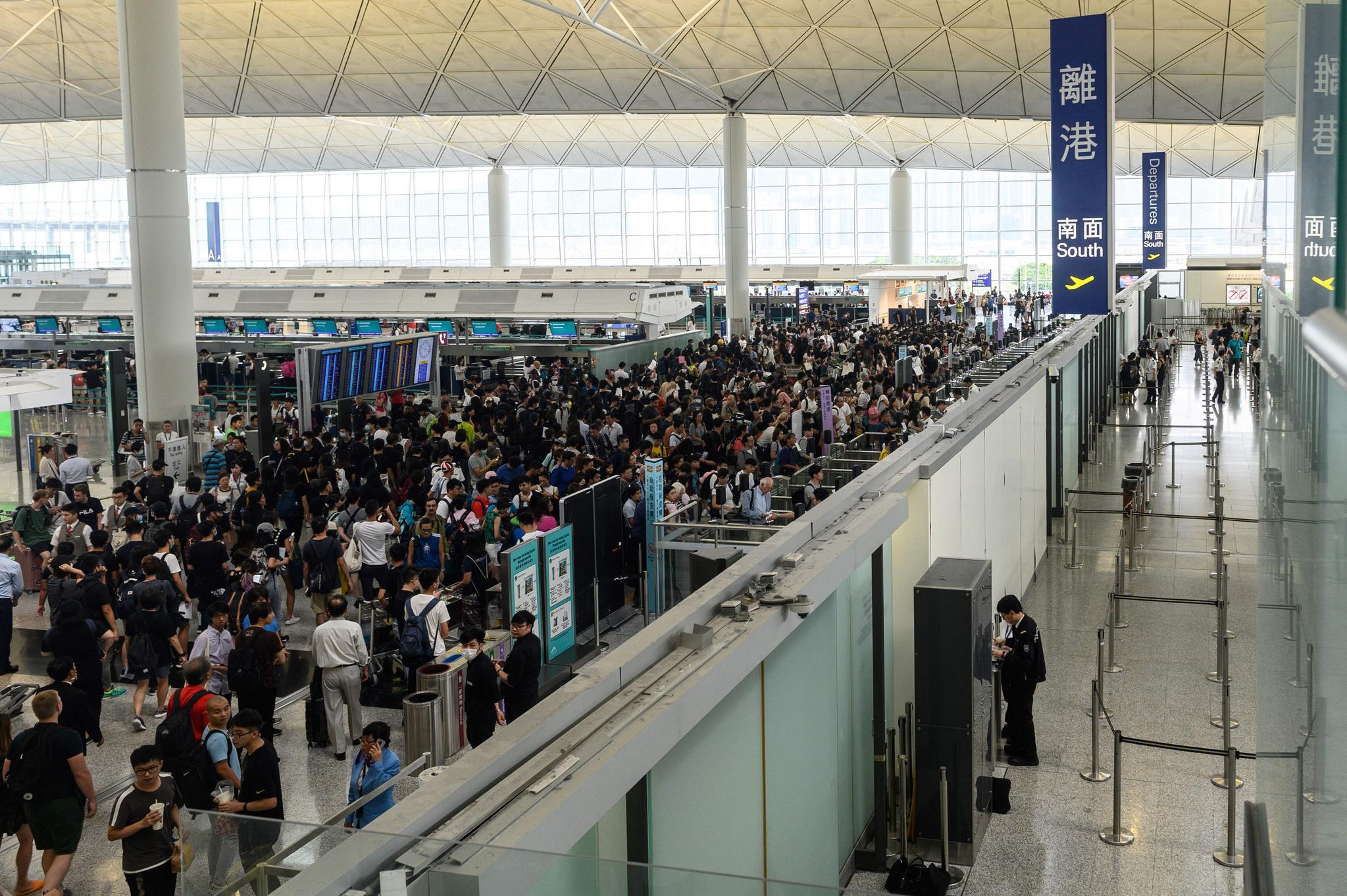 시위대가 13일 홍콩국제공항 출구 게이트를 막으면서 여행객들이 큰 불편을 겪었다. [AFP=연합뉴스]