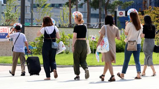 대구·경북 일부 지역은 일주일 째 폭염경보가 이어지고 있다. 13일 오후 35도를 넘긴 대구광역시 동대구역 인근에서 시민들이 부채로 햇볕을 가린 채 지나가고 있다. [뉴스1]