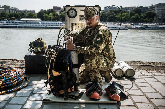 라즐로 토로크 사령관이 지난 7 월 3 일 헝가리 부다페스트 마가렛 섬에서 잠수 장비를 점검하고 있다. 한국 잠수팀과 잠수 장비를 공유하며 유기적으로 시신 수습, 인양 작업 등을 수행해냈다. [EPA=연합뉴스]