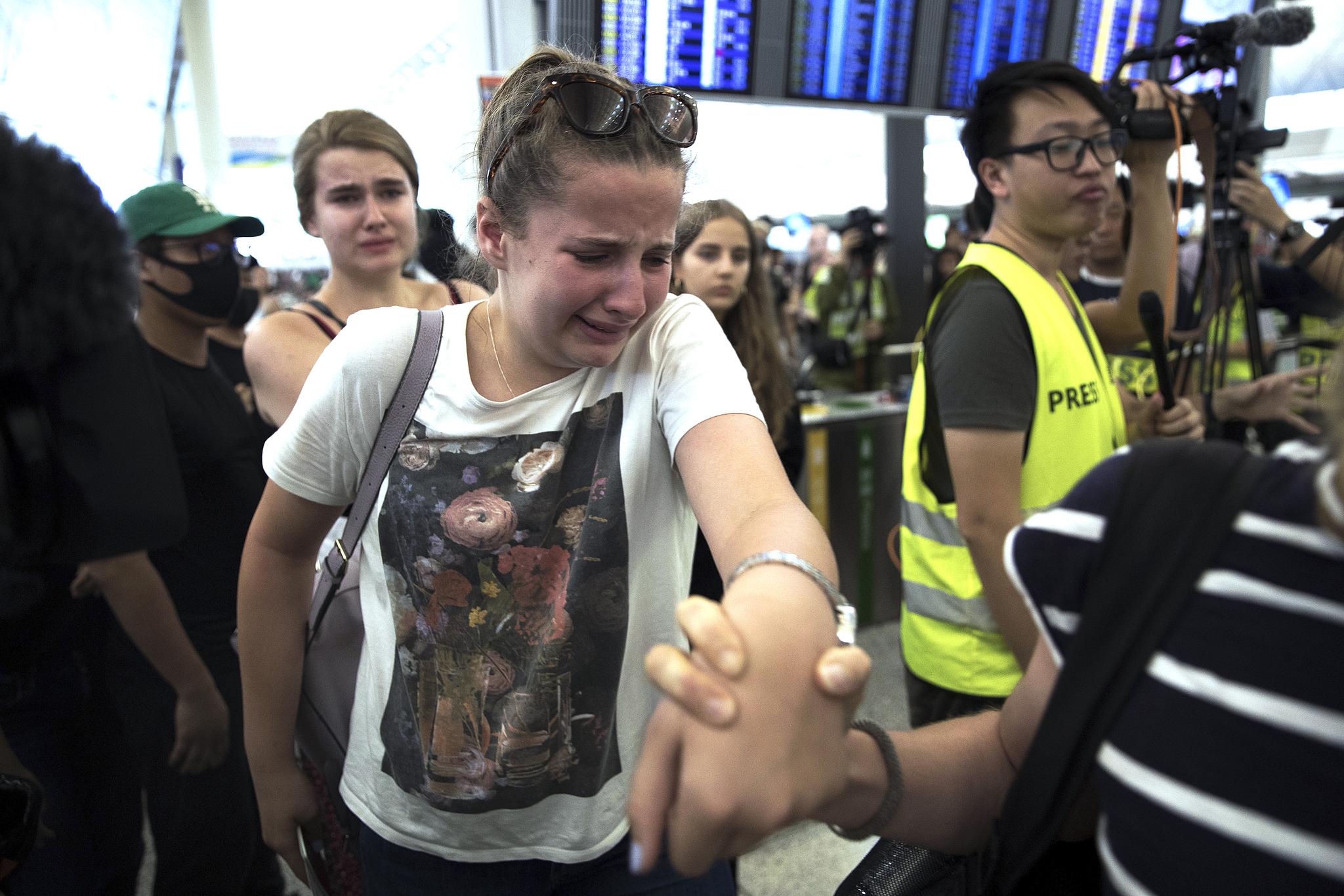 비행기를 놓칠 것을 걱정하는 한 여행객이 시위대 사이를 지나가며 울먹이고 있다. [AP=연합뉴스]