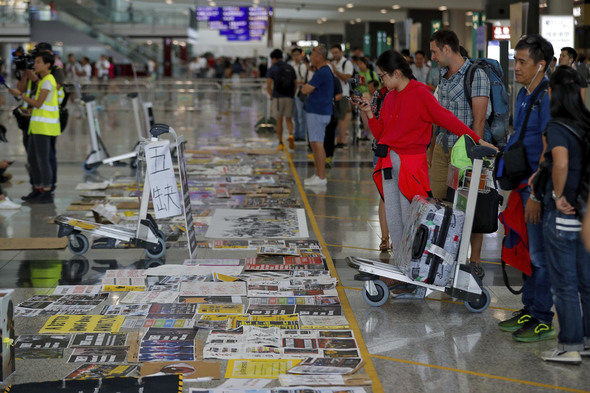 14일 여행객들이 홍콩공항 로비에 시위대들이 깔아놓은 유인물들을 살펴보고 있다.[AP=연합뉴스]