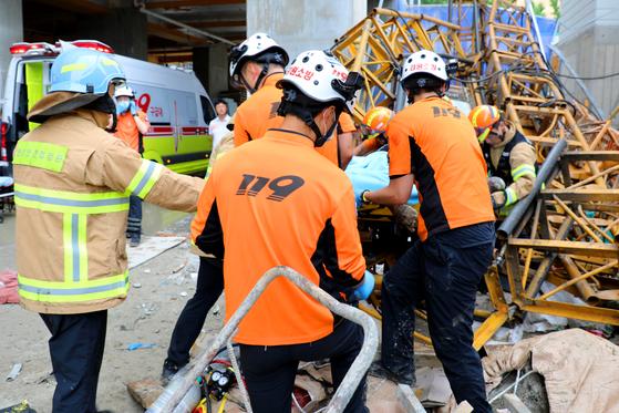 14일 강원도 속초시 조양동 스타힐스 아파트 공사현장 15층에서 공사용 엘레베이터가 추락해 소방대원들이 부상자를 구조한 뒤 병원으로 이송하고 있다. [뉴스1]