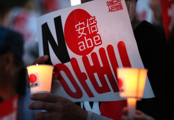 지난 10일 오후 서울 종로구 옛 주한 일본대사관 앞에서 열린 '아베규탄 4차 촛불문화제'에서 참가자들이 촛불을 들고 있다. [연합뉴스]