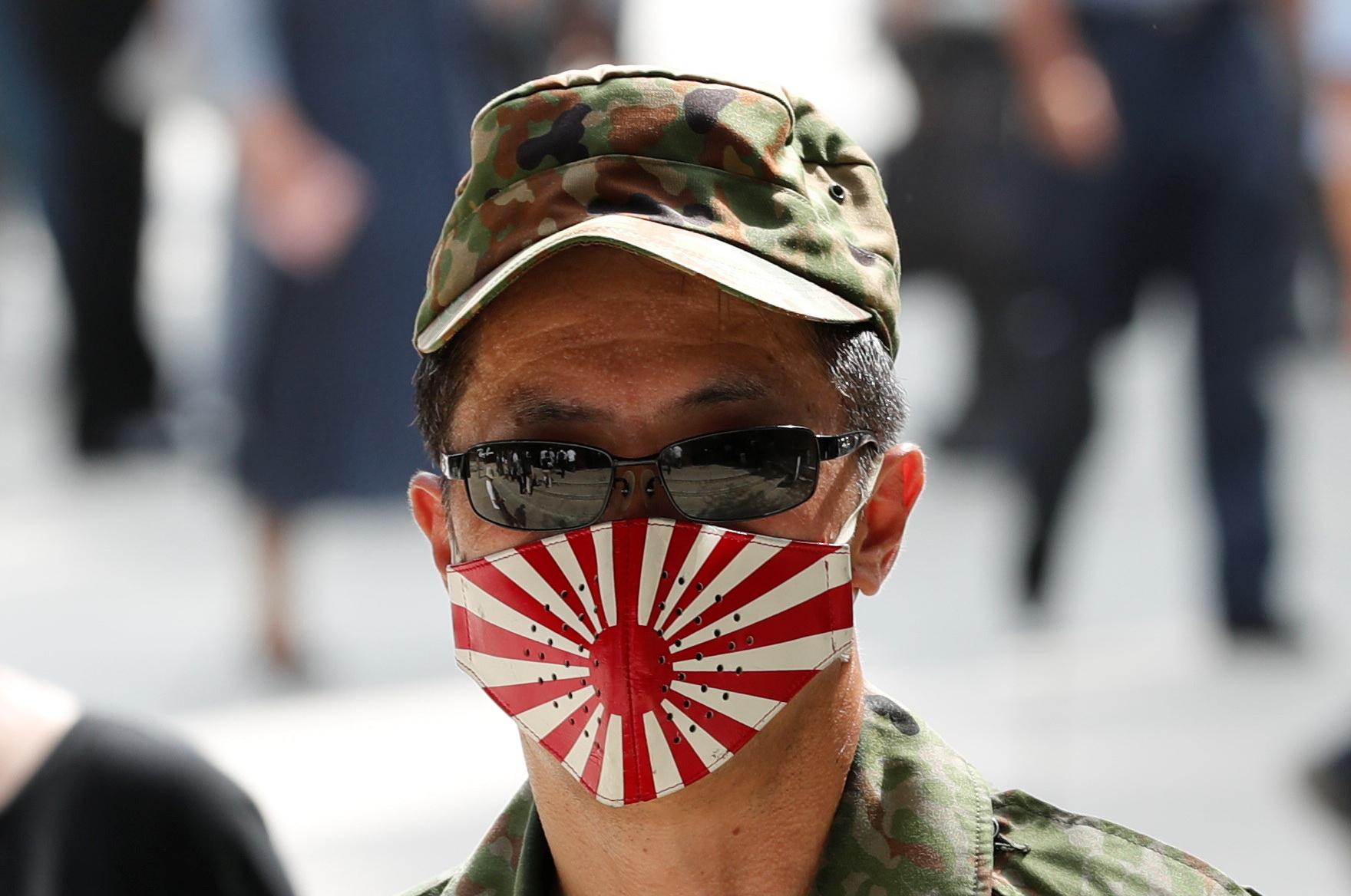 일본 우익 인사가 15일 전범기인 욱일기로 디자인한 마스크를 쓰고 도쿄 야스쿠니 신사를 참배하고 있다. [REUTERS=연합뉴스]