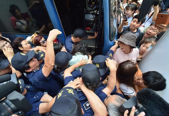 지난 12일 오전 제주지법에서 고유정(36)의 첫 공판이 열린 가운데 시민들이 호송차에 오르는 고유정의 머리채를 잡아 당기고 있다. [뉴시스]