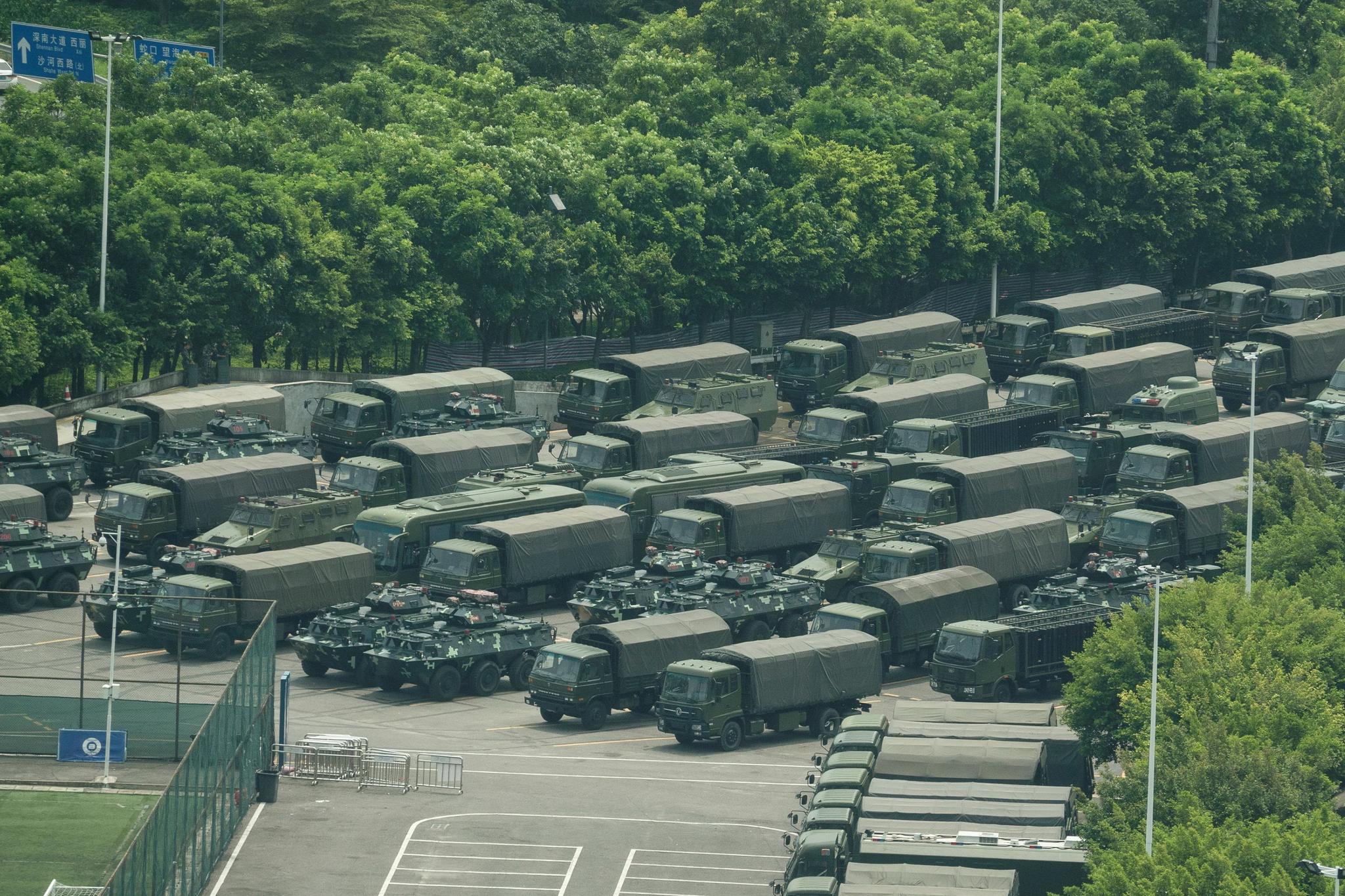 군용 트럭과 병력 수송 장갑차량이 15일 홍콩 인근 광둥성 선전의 스타디움에 도열해 있다. 이날 아침 스타디움에서 수천명의 중국군이 훈련하는 모습이 목격돼 홍콩사태에 무력 개입하는 것이 아닌가 하는 공포를 불러일으켰다.[AFP=연합뉴스]