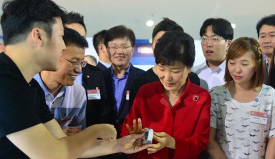 박근혜 전 대통령이 2015년 8월 한국과학기술원(KAIST)에서 열린 창조경제혁신센터 페스티벌 개막식에 참석해 청년 창업자로부터 시각장애인용 스마트 워치의 설명을 듣고 있다. [당시 청와대]