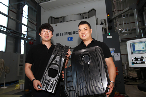 한국탄소융합기술원 연구원들이 국내 완성차 업체와 협업해 개발한 자동차 내장용 탄소섬유 부품을 들어보이고 있다. 전주=이동현 기자