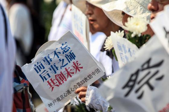 15일 중국 동부 장쑤성 난징(南京) 학살 희생자 위령관에서 열린 희생자 추모 평화집회에 한 시민이 팻말을 들고 있다.[AFP=연합뉴스]