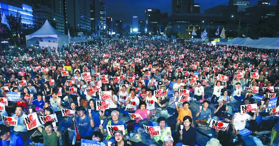 15일 오후 서울 광화문광장에서 열린 '8·15 아베 규탄 범국민 촛불문화제'에 참석한 시민들이 손피켓과 촛불을 들고 일본 아베 정권의 역사 왜곡과 경제 보복 조치를 규탄하고 있다. 최승식 기자