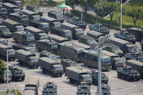 중국 군용 트럭과 장갑차들이 15일 홍콩과 10분 거리인 중국 선전만(灣)의 한 경기장 외곽에 집결해 있다. 선전만은 다리로 홍콩 북쪽의 신계(新界) 지역과 연결된다. AFP통신은 이날 수천 명 규모의 중국 병력이 붉은 깃발을 흔들며 퍼레이드를 했다고 보도했다.