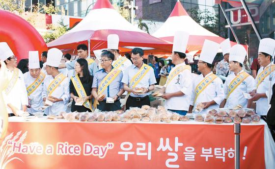 농림부와 농협은 오는 18일 광주 프로야구 경기에서 '쌀의 날' 기념행사를 개최한다. 사진은 지난해 제과협회와 공동으로 서울 강남역에서 아침 식사용 쌀빵을 나누고 있는 모습. [사진 농림부]