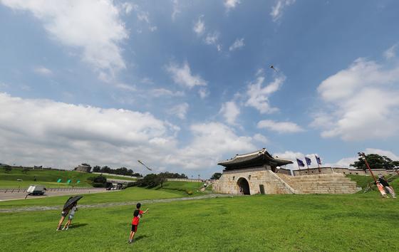 16일 오후 경기도 수원시 세계문화유산 화성(華城) 창룡문을 찾은 어린이들이 연을 날리고 있다. 이날 전국이 비가 그친 뒤 구름많은 날씨를 보였다. [연합뉴스]