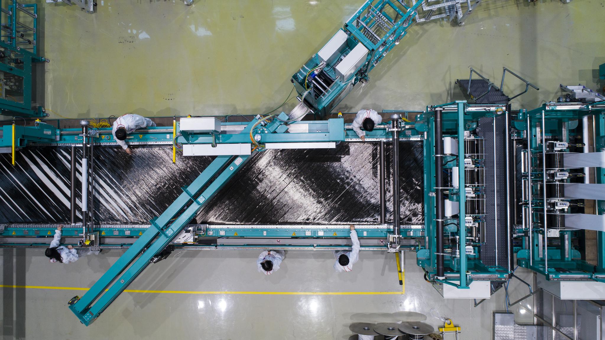 한국탄소융합기술원 연구원들이 탄소섬유 직조장비로 탄소섬유를 짜고 있다. 여기에 수지를 입히고 성형하면 우리가 흔히 보는 탄소섬유가 된다. [사진 한국탄소융합기술원]