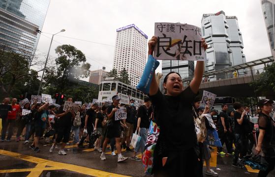 홍콩의 교사들이 폭우가 내린 17일 오후(현지시간) 홍콩 도심인 센트럴지역 차터공원에서 집회를 열고 '범죄인 인도 법안'(송환법) 반대 집회 참가 학생들의 안전을 요구하며 정부청사 방향으로 행진하고 있다. [연합뉴스]