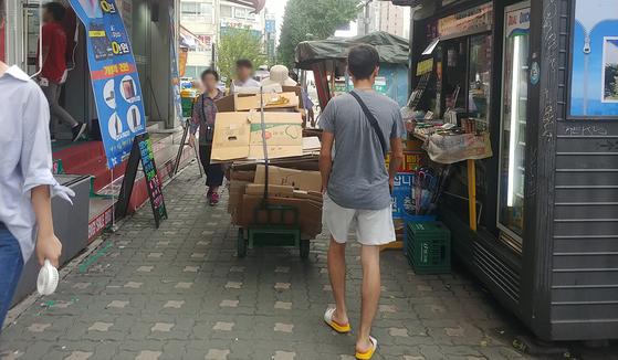 지난 16일 서울 서대문구 신촌에서 보도위로 폐지줍는 노인이 손수레를 끌고 가고 있다. 도로교통법상 차로 분류되는 손수레는 보도위로 통행할 경우 불법이며 3만원의 범칙금을 물게된다. 박해리 기자