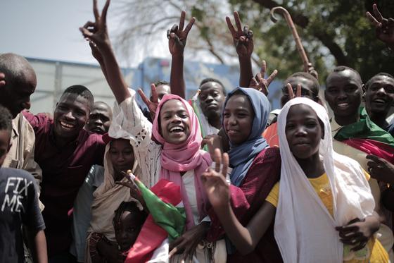 수단 국민들이 17일(현지시간) 수도 하르툼 우정관에서 권력이양 협정 서명 소식이 알려진 뒤 기뻐하고 있다. [AFP=연합뉴스]