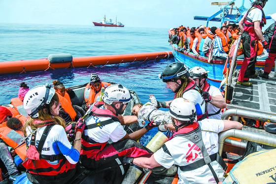 지난해 지중해에서 난민구조 비정부기구(NGO)인 'SOS 지중해' 소속 대원들이 한 아기를 구조하고 있다. 구조된 아기가 탄 목선은 리비아 해안에서 약 50㎞ 떨어진 해상에서 발견됐으며 250명 이상이 타고 있었다. [EPA=연합뉴스]