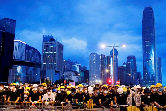 지난 1일 홍콩 시위대가 중국 반환 기념식장 주위에서 바리케이드를 치고 대기 중이다. 모두가 마스크와 헬멧, 고글을 착용하고 있다. 보안 당국의 감시에 맞서 신원이 노출되지 않도록 막는 복장이다. [로이터=연합뉴스]