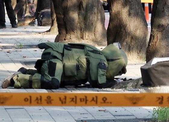 19일 서울 여의도 국회 외곽 7문 건너편, 서강대교 남단 사이에 폭발물 의심 물체 관련 신고를 받은 경찰 폭발물 제거반이 폭발물이 있는지 살펴보고 있다. [뉴시스]
