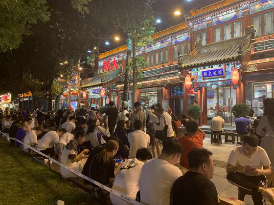 지난 3일 자정께 베이징 야식거리 구이제의 한 민물가재요리 전문식당 앞에 400여 팀의 대기자들이 간이 의자에 앉아 해바라기씨를 까먹으며 기다리고 있다. 신경진 기자