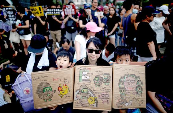 18일 오후(현지시간) 홍콩에서 열린 송환법 반대 시위에 참여한 한 여성과 아이들이 경찰의 과잉진압을 규탄하는 그림을 들고 있다. [로이터=연합뉴스]