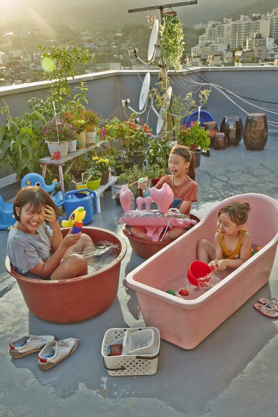 영화 '우리집' 한 장면. 맨 왼쪽이 주인공 하나다. 유미, 유진 자매네 옥탑에서 즐거운 물놀이. [사진 롯데엔터테인먼트]